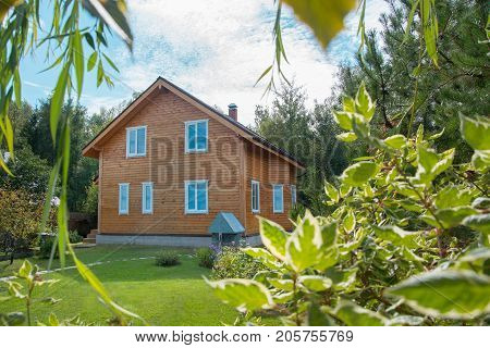 House in the countryside in summer. The Moscow region. Contemporary house in Russia. There is two-story house of timber. There are tiny green lawns in front of the houses paths to the house are visible. House have nice landscaping with shrubs and blooming