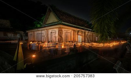 Taar Yo Temple Songkhla Thailand - May 10 2017 : Buddhists walking with lighted candles in hand around a temple to pay respect to the Triple Refuges long exposure