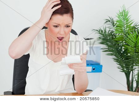 Young Attractive Red-haired Female Being Surprised By The Amount Of The Receipt