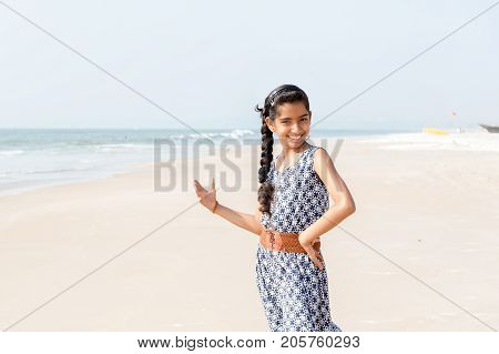 Portrait of beautiful indian teenage female wearing in a dress on the beach in sunlight. High key image.