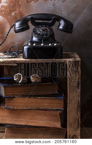Dusty vintage bakelite phone on a wooden fruit box with old books and sea shells.