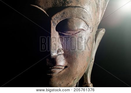 Spiritual enlightenment. Buddha head with divine light. Bronze statue face in close up against black background with copy space.