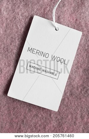 Clothes label lettered merino wool on pink wool background closeup