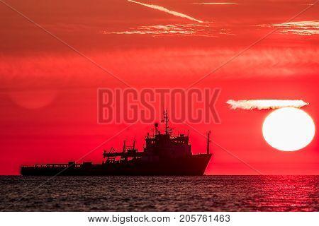 Travel destination. Red dawn at sea. Fishing trawler boat silhouette on tropical waters at sunrise. Dawn on an idyllic sea.