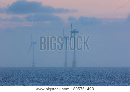 Offshore wind farm on a misty morning at sunrise. Fog and cloud on the ocean horizon with three giant power turbines in front of pastel colored sky. Cool tranquil environment scene at sea.
