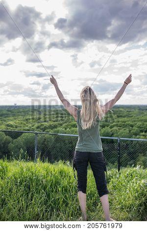 Woman arms raised up to sky,dramatic sky