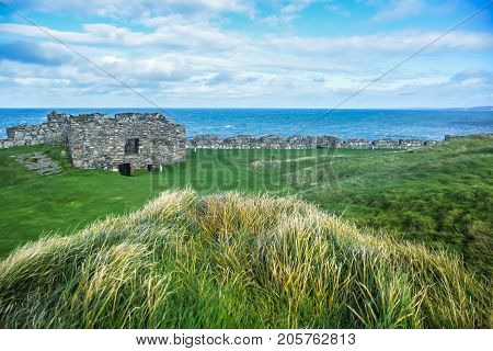 The remains of Peel Castle's wall on top of Peel hill covered with green grass on the ground, Isle of Man