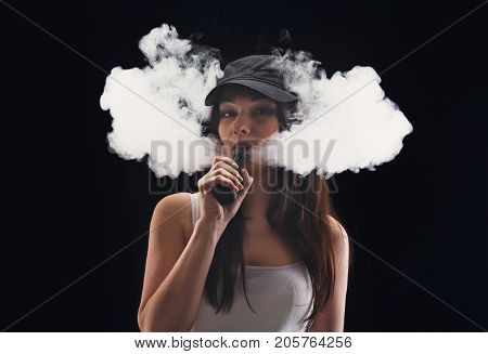 Young woman in a cloud of vape smoke on black background. Hipster girl in cap smoking e-cigarette to quit tobacco. Vapor and alternative nicotine free smoking concept, copy space