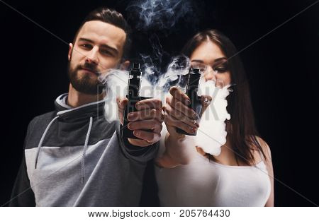 Couple vaping. Young man and woman blowing smoke to join it in one cloud and showing their vapes to camera at black studio background. Relationship and vape addiction concept with copy space