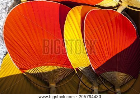 Setting of handheld fans for wedding guests. Red and yellow bamboo rigid fans