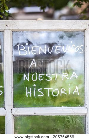 Optimist phrase written over old windows glasses in spanish. Welcome to our story (traslation)