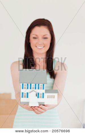Ziemlich Rothaarige Frau gedrückt halten ein Miniatur-Haus und auf dem Boden stehend