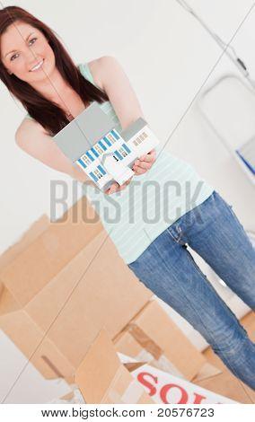 Hübsche rothaarige Frau gedrückt halten ein Miniatur-Haus und auf dem Boden stehend