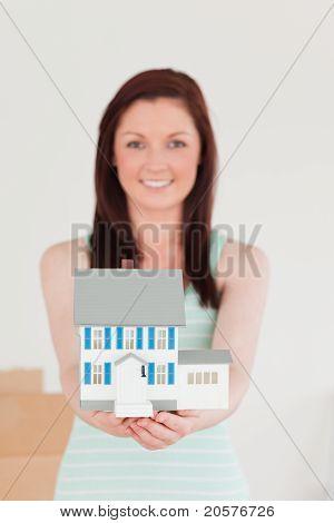 Niedliche Rothaarige Frau gedrückt halten ein Miniatur-Haus und auf dem Boden stehend