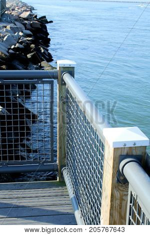 Wood and wire fencing built on top of jetty rocks to provide a safe overlook over a dangerous channel.
