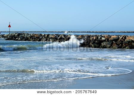 Small waves crashing along a jetty on the incoming tide.