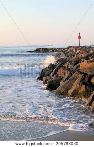 Small waves crashing against a rock jetty.