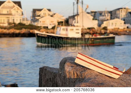 Miniature wooden toy rowboat sitting on a jetty in front of large fishing boat.