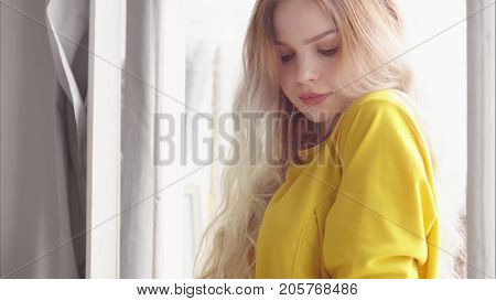 A beautiful woman in a yellow dress with long hair stands by the window and holds her hand over the window frame