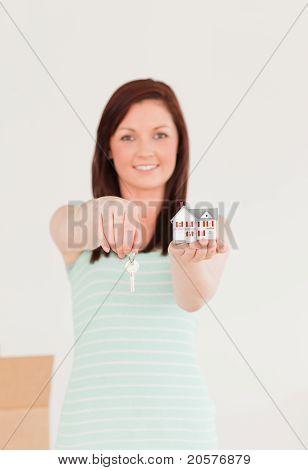 Gut aussehende Rothaarige Frau hält einen Schlüssel und ein Miniatur-Haus auf dem Boden stehend