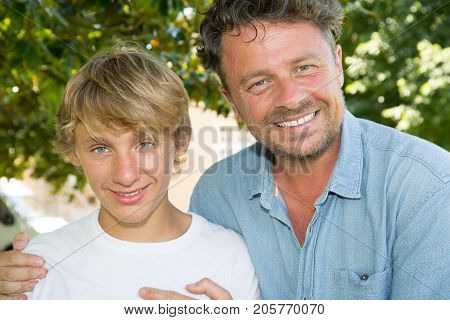 Proud And Smile Father With Teenager Son Outdoors