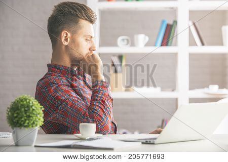 Portrait of thoughtful young man sitting at desk with laptop coffee cup plant and other items