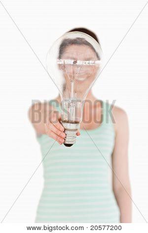 Ziemlich Rothaarige Frau hält eine Glühbirne-Haus stehen