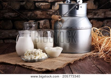 milk products. tasty healthy dairy products on a table on. sour cream in a bowl cottage cheese bowl cream in a a bank and milk jar glass bottle and in a glass