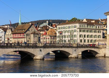 Zurich, Switzerland - 25 September, 2017: people on the Munsterbrucke bridge over the Limmat river, old town buildings in the background. Zurich is the largest city in Switzerland and the capital of the Swiss canton of Zurich.
