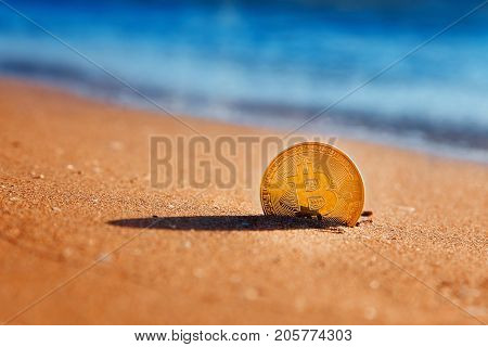 Bitcoin. Bitcoin on golden sand, in background sea. Concept freelance, stock exchange.