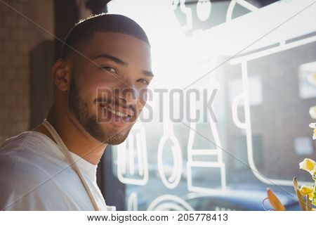 Portrait of smiling young waiter by window in cafe