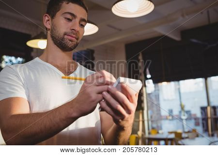 Young waiter taking order while standing in cafe