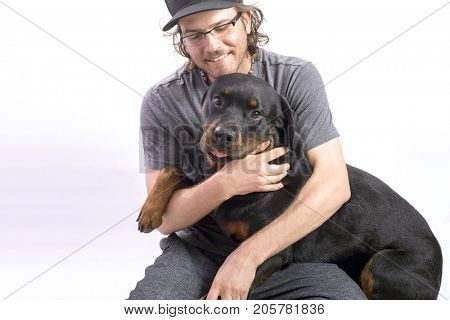 Happy dog owner holding a rottweiler with sweet expression isolated on white background