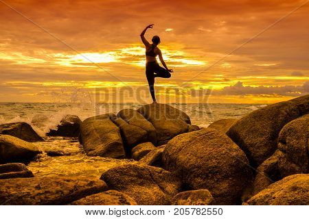 Yoga on the rock at the sunset with the murmur of waves