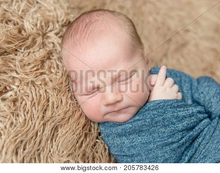 Little kid wrapped in a blue scarf  resting, topview