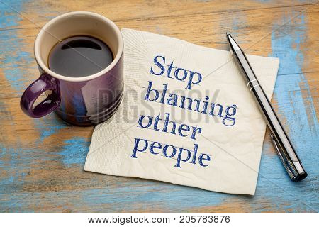 Stop blaming other people advice or reminder - handwriting on a napkin with a cup of espresso coffee