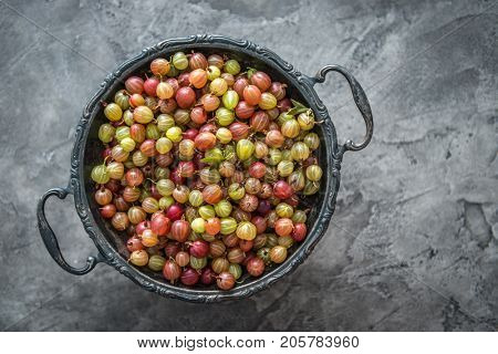 Huge bowl full of fresh ripe gooseberries, yellow greenish and red, additional copyspace, topview