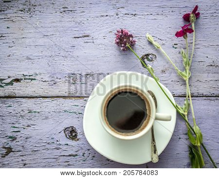 Cute field wild flowers, daisies and clover, a cup of black coffee, copyspace, topview
