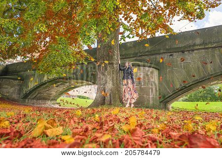 Autumn image with a young woman in a modern dress and a black jacket staying under a tall tree and watching the colorful falling leaves.