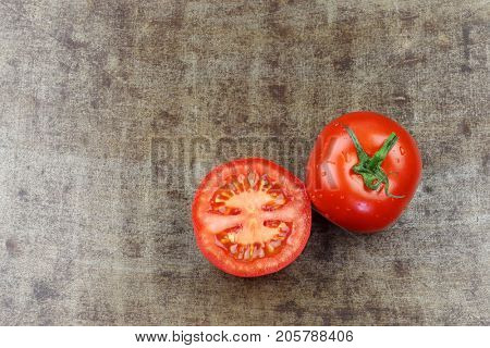 fresh  tomato and a cut one on a grungy metal background