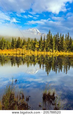 Patricia Lake reflects the snowy peak of the Pyramid Mountain. Indian summer. The concept of extreme and ecotourism