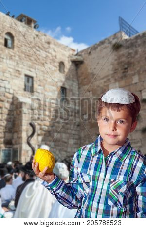 The greatest shrine of Judaism is the Western Wall of the Temple. Autumn Jewish holiday Sukkot. Beautiful Jewish boy with green eyes, in white skullcap, with etrog in his hand