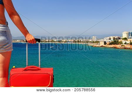 Woman with red suitcase close-up. Girl with suitcase against mediterranean sea background. Traveling background with copy space on emerald sea water backdrop.