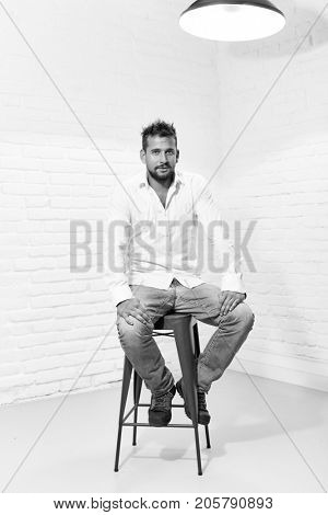 Black and white full length indoor portrait of handsome man in casual cloth sitting on barstool.