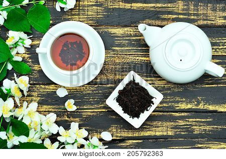 Black tea in a round white cup with saucer and white tea pot on a wooden background top view