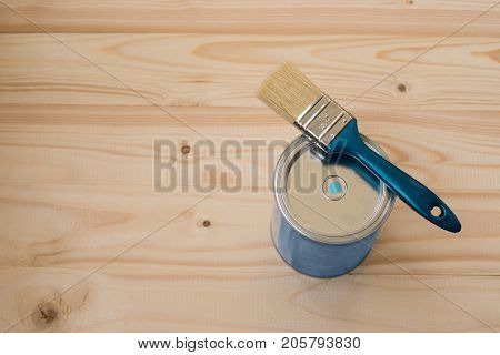 Blue paint and brush on wooden background, top view. Home improvement paint brush and opened can of blue paint. Bank blue paints and brush on a wooden background. brush and paint on a wooden background.