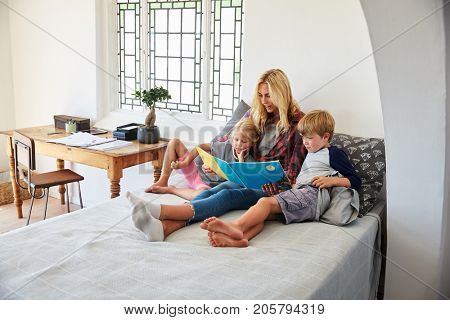 Mother With Children Sitting On Bed Reading Book Together