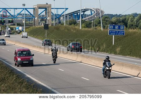 LE HAVRE FRANCE - AUGUST 24 2017: Toll station Pont de Normandie over river Seine with passing cars and a motorcyclist making a wheelie