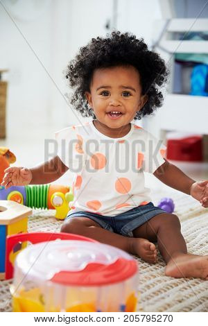 Portrait Of Baby Girl Having Fun In Playroom With Toys