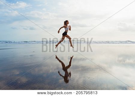 Barefoot sporty girl with slim body running along sea surf by water pool to keep fit and health. Beach background with blue sky. Woman fitness jogging sports activity on summer family vacation.